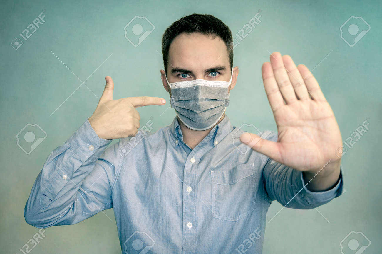 Mandatory wearing of a mask in a public place. Warning. Portrait of serious man show stop sign gesture warn people stay home wear medical over bright color background - 173227053