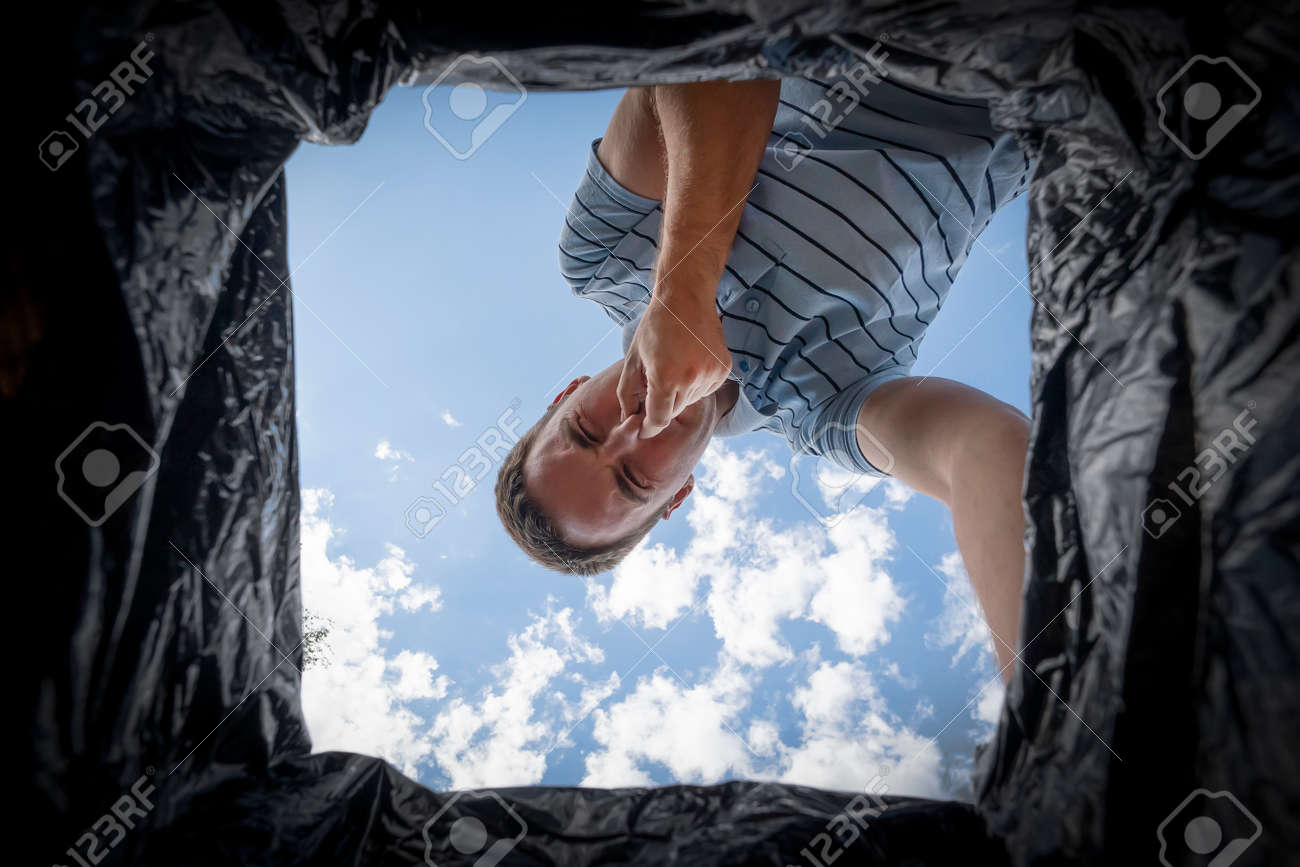 The man looks into the trash can and covers his nose from the strong stench. - 173227174