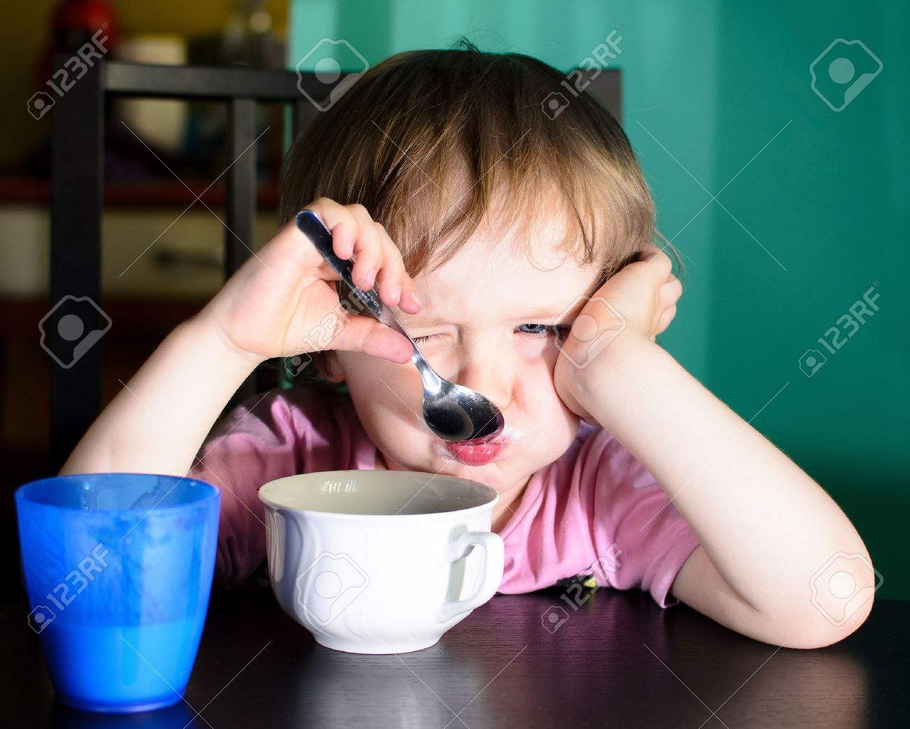 Nervous little boy eating and drinking milk Stock Photo - 14426106