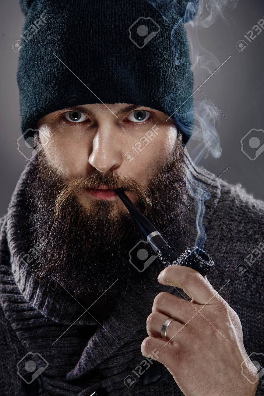 bb0e204bc83 Portrait of a man with a beard the smoking a pipe. A man looks like