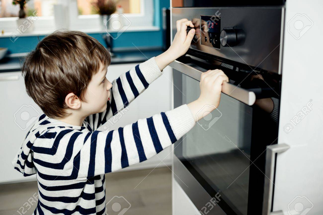 High Quality Curious Little Boy Dangerously Playing With The Knobs On The Oven. Danger  At Home Stock