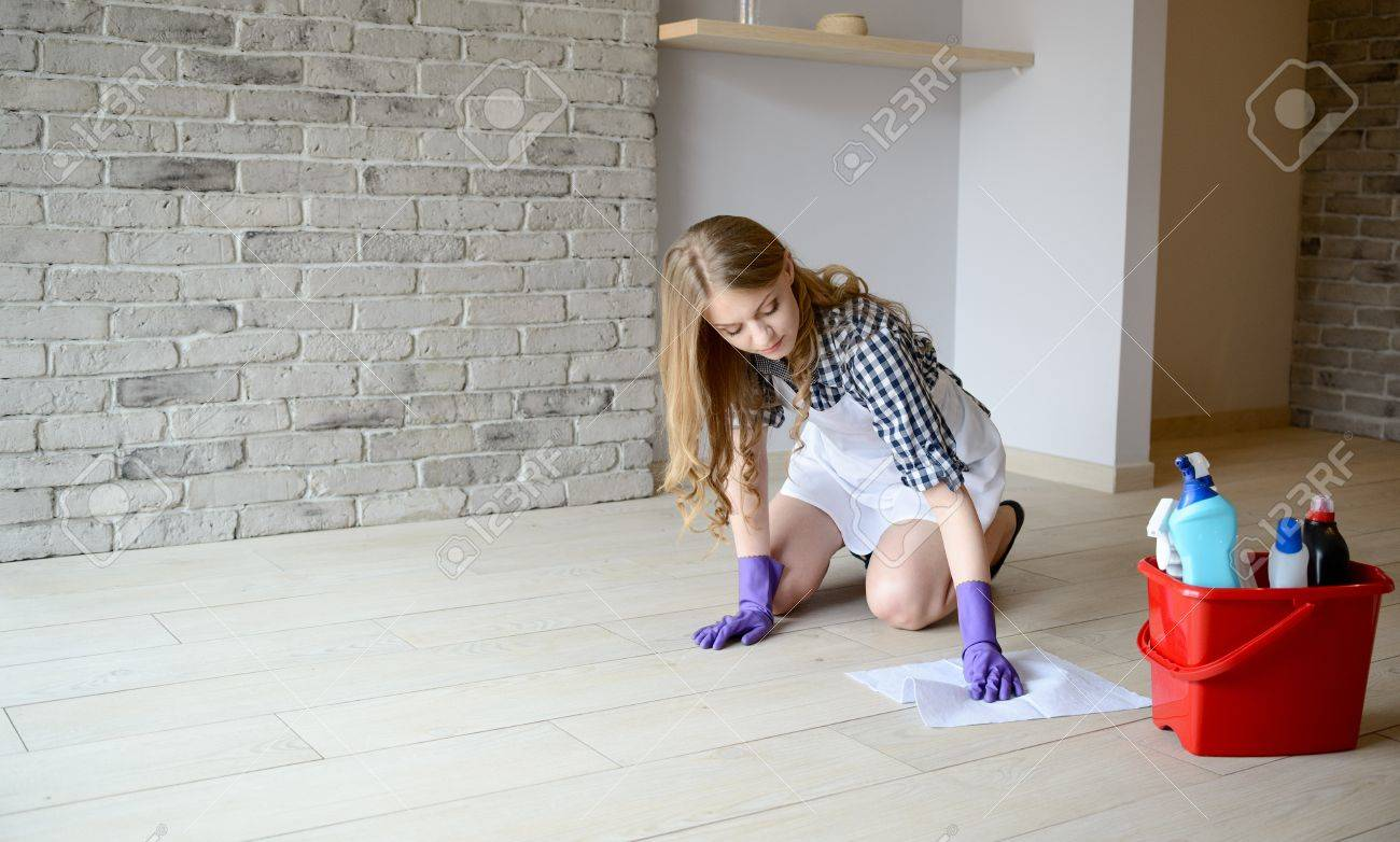 White rubber apron - Stock Photo Woman Washes The Floor In The Room On Her Knees Dressed In A White Apron And A Plaid Shirt Protective Rubber Gloves On Her Hands