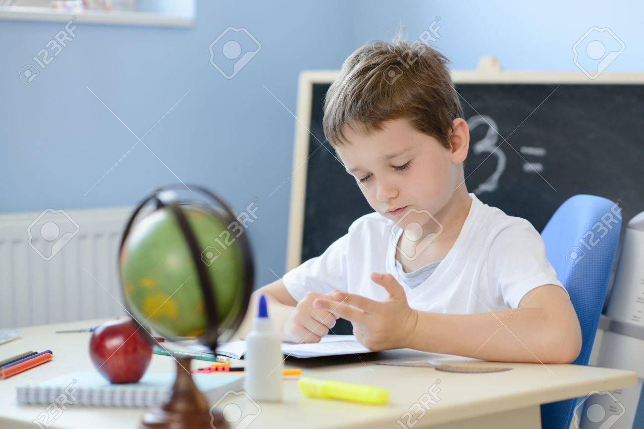 7 years old boy solves multiplication table in his copybook and counting on fingers. Back to school - 61918198