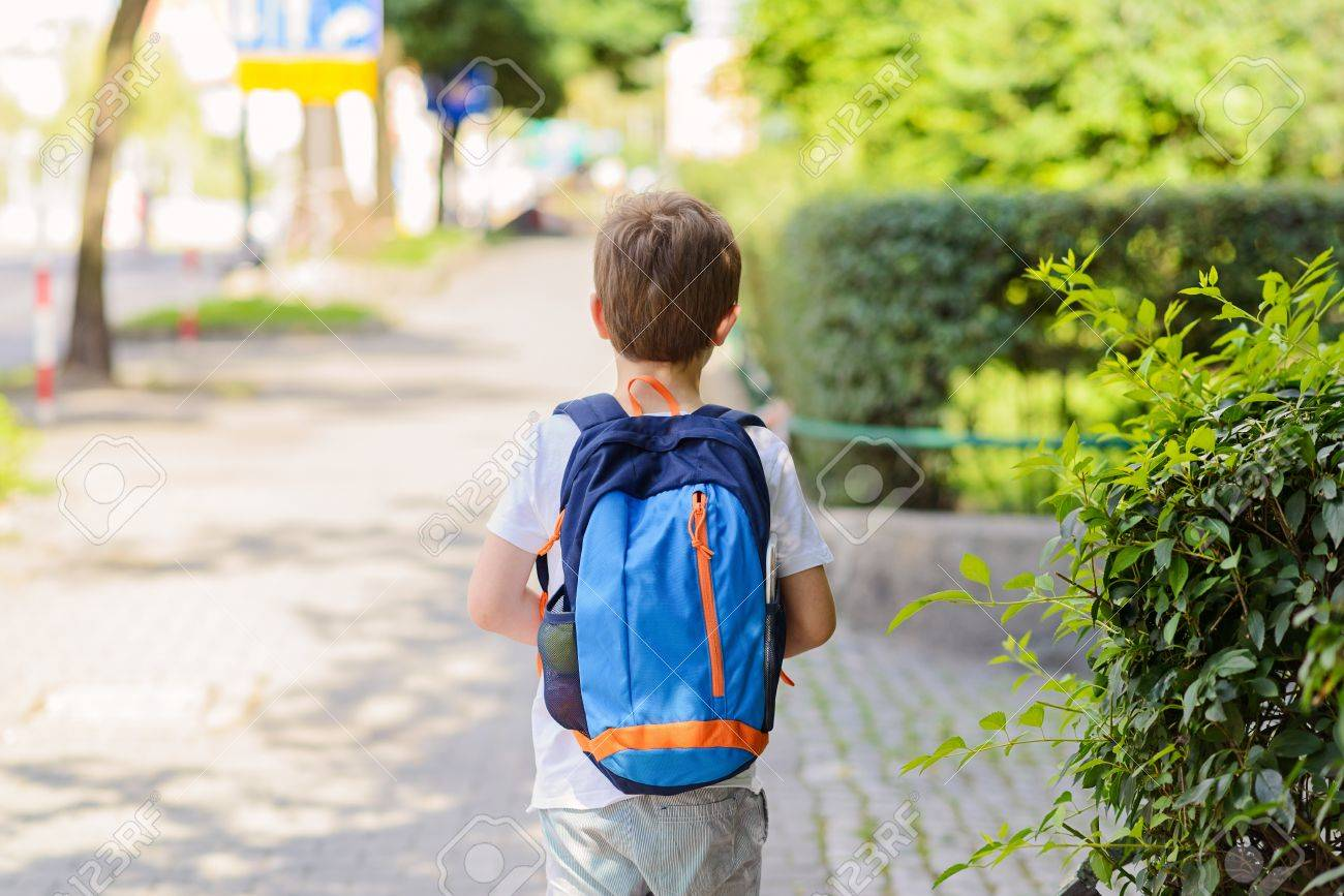 Little 7 years schoolboy going to school. Dressed in white t shirt and shorts. Blue backpack - 61939110