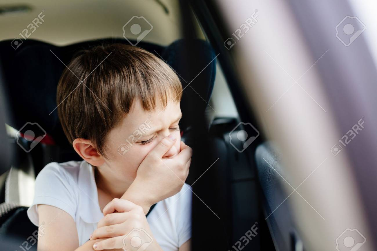 Seven years old small child in the backseat of a car sitting in children safety car seat covers his mouth with his hand - suffers from motion sickness - 63663287
