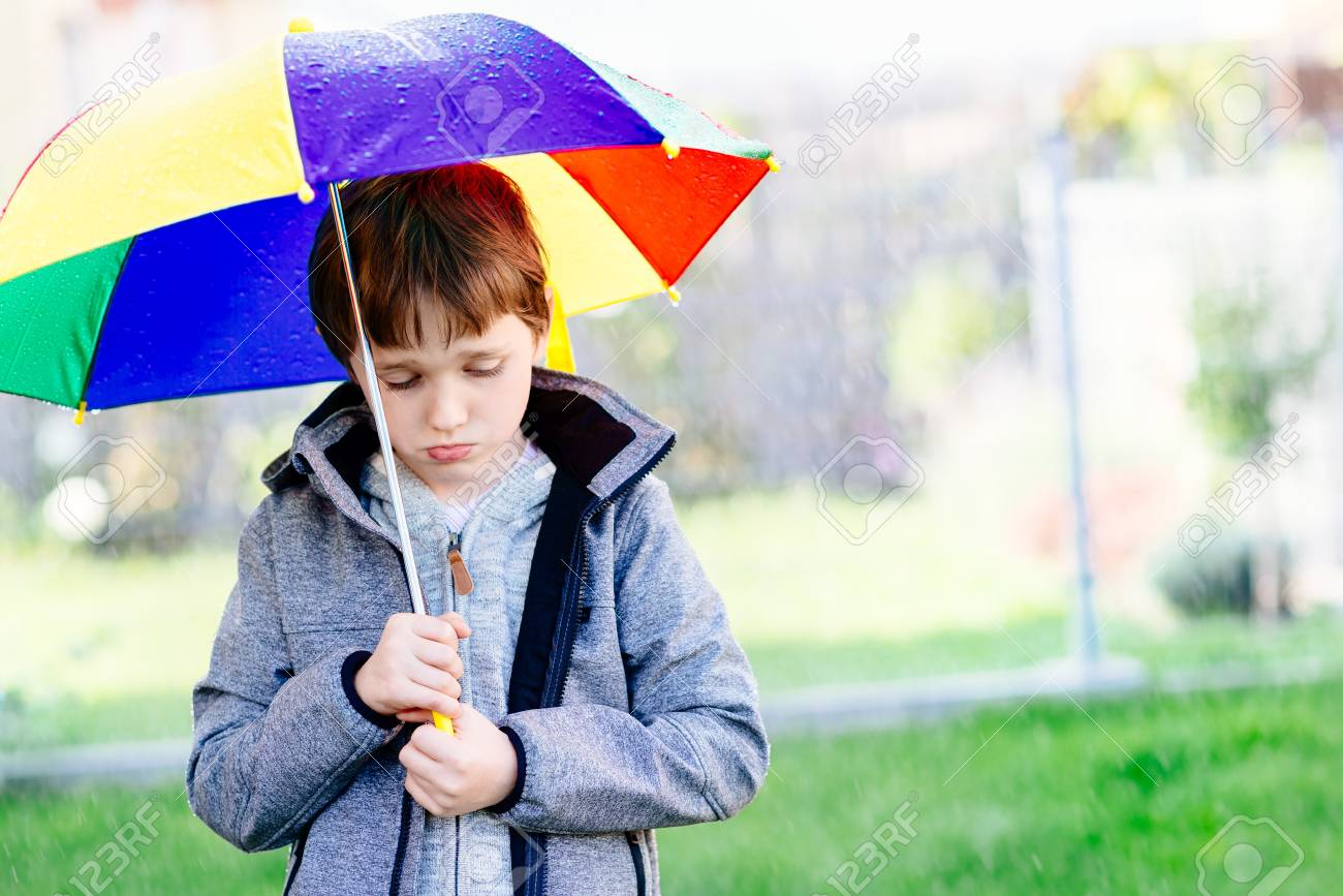 seven years old boy standing at the rain with colorful umbrella