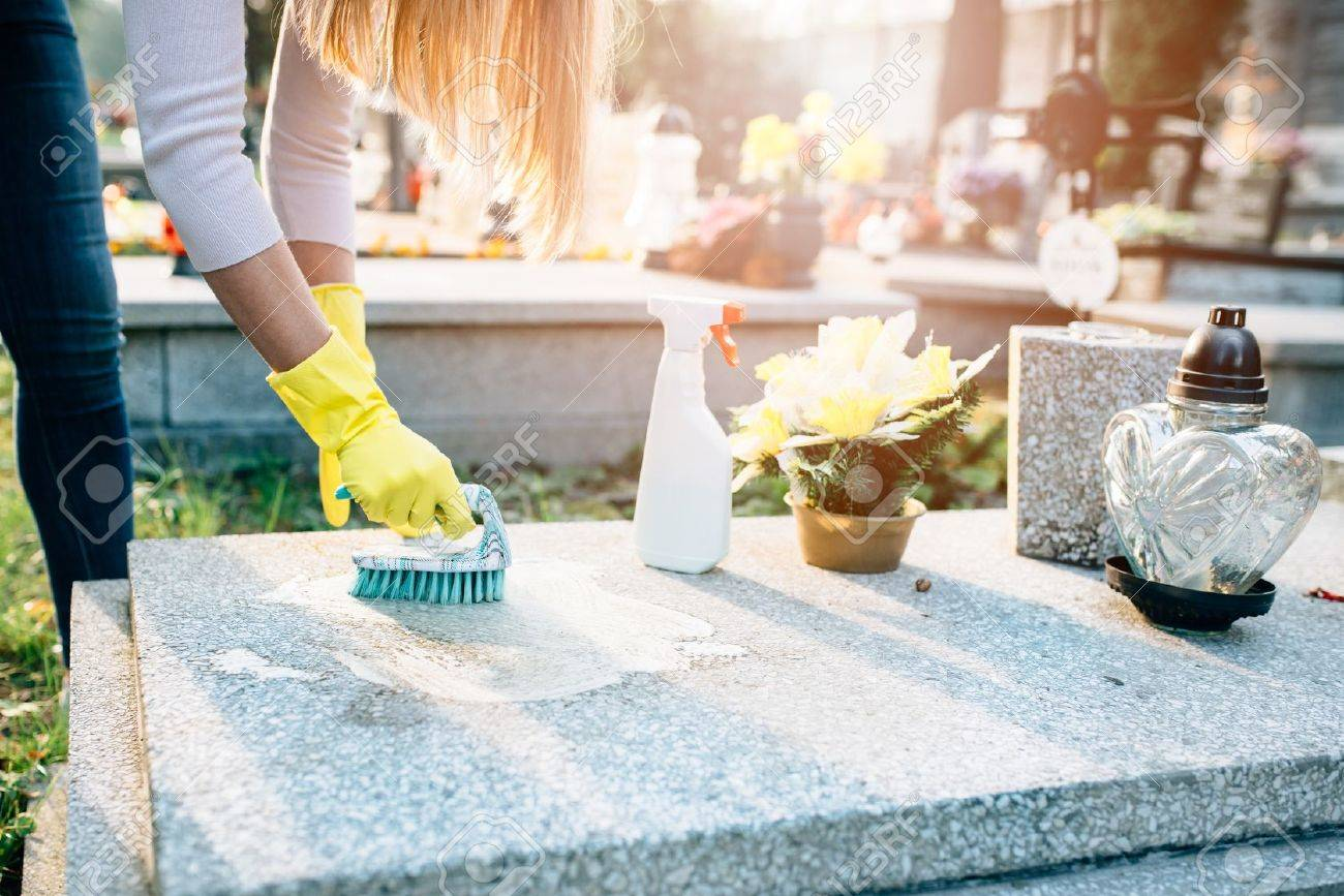 A woman cleans the grave. Washing tombstone with brush. Preparations for All Saints Day on November 1 - 63677640