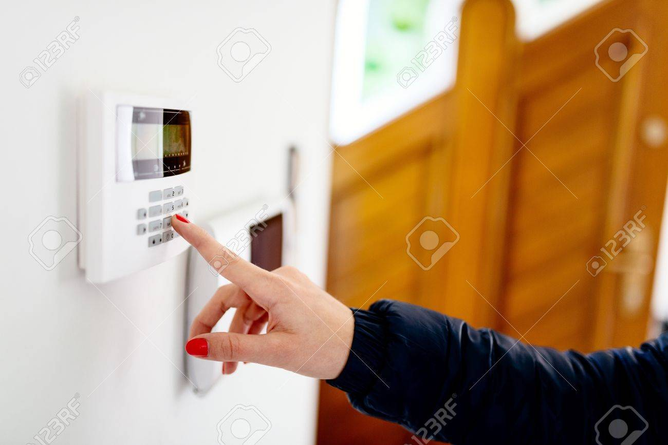 Young woman entering security code on home security alarm system keypad - 66755652