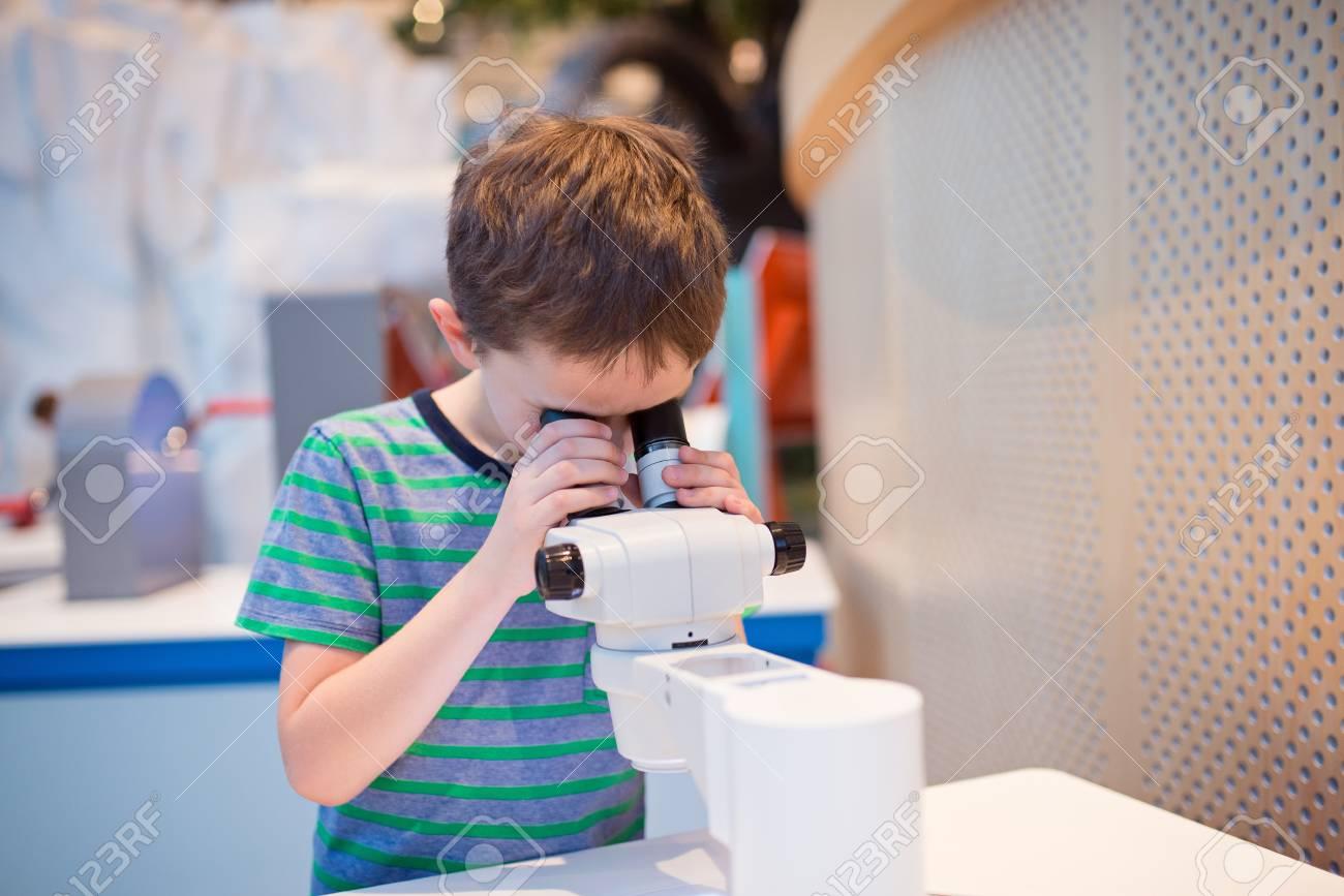 Kleine kind junge blick durch mikroskop in der schule lizenzfreie
