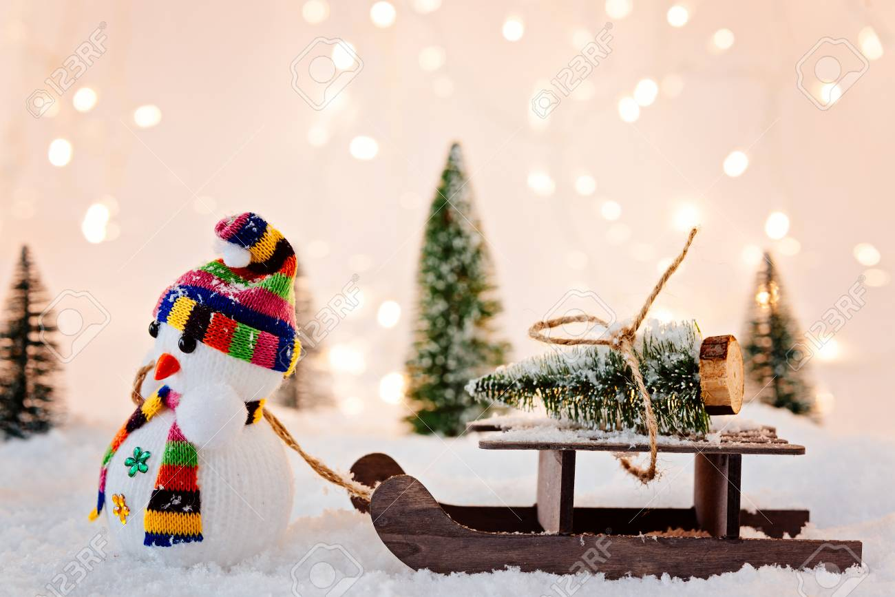 Toy Snowman Pulling Small Wooden Sleigh With A Christmas Tree