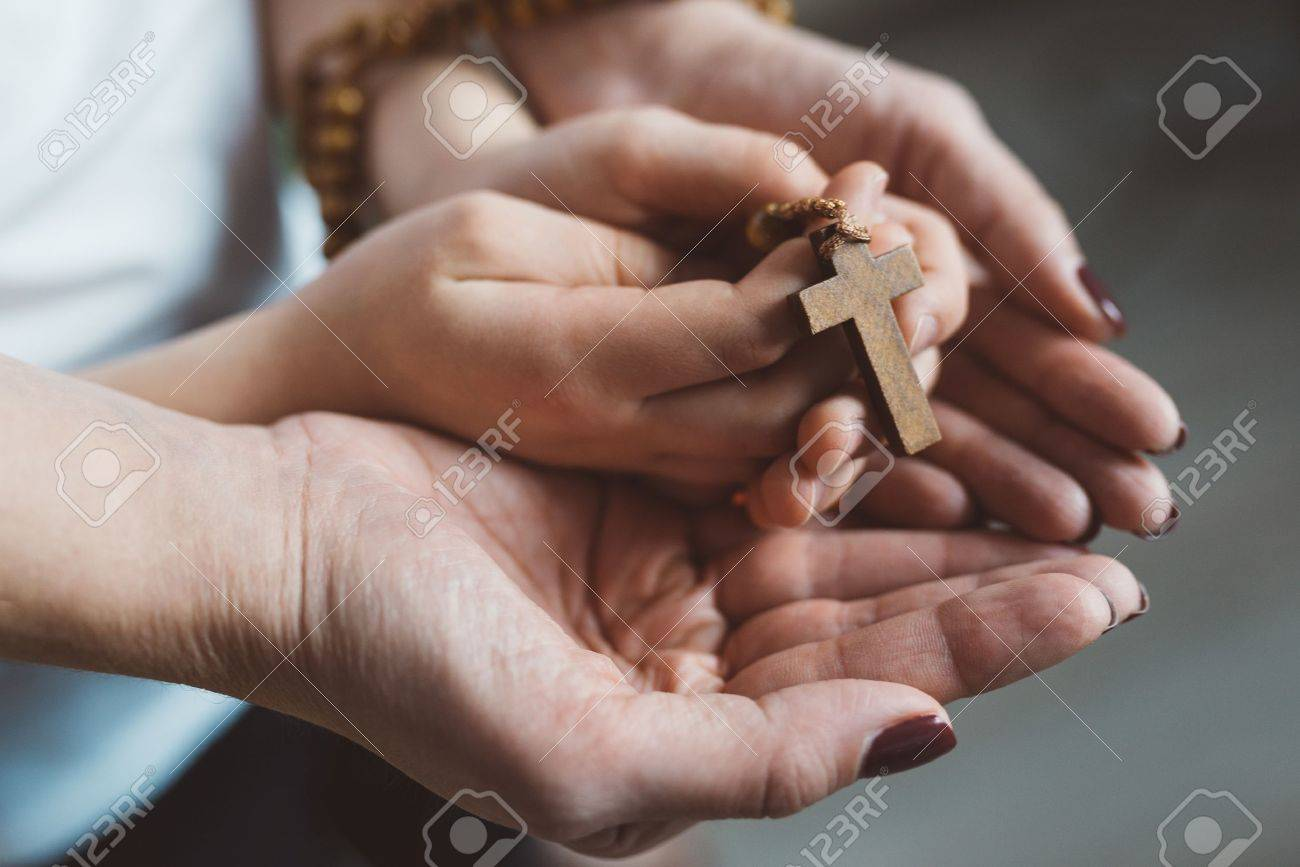 Family prayer. Mother and child hands with wooden rosary - 67235998