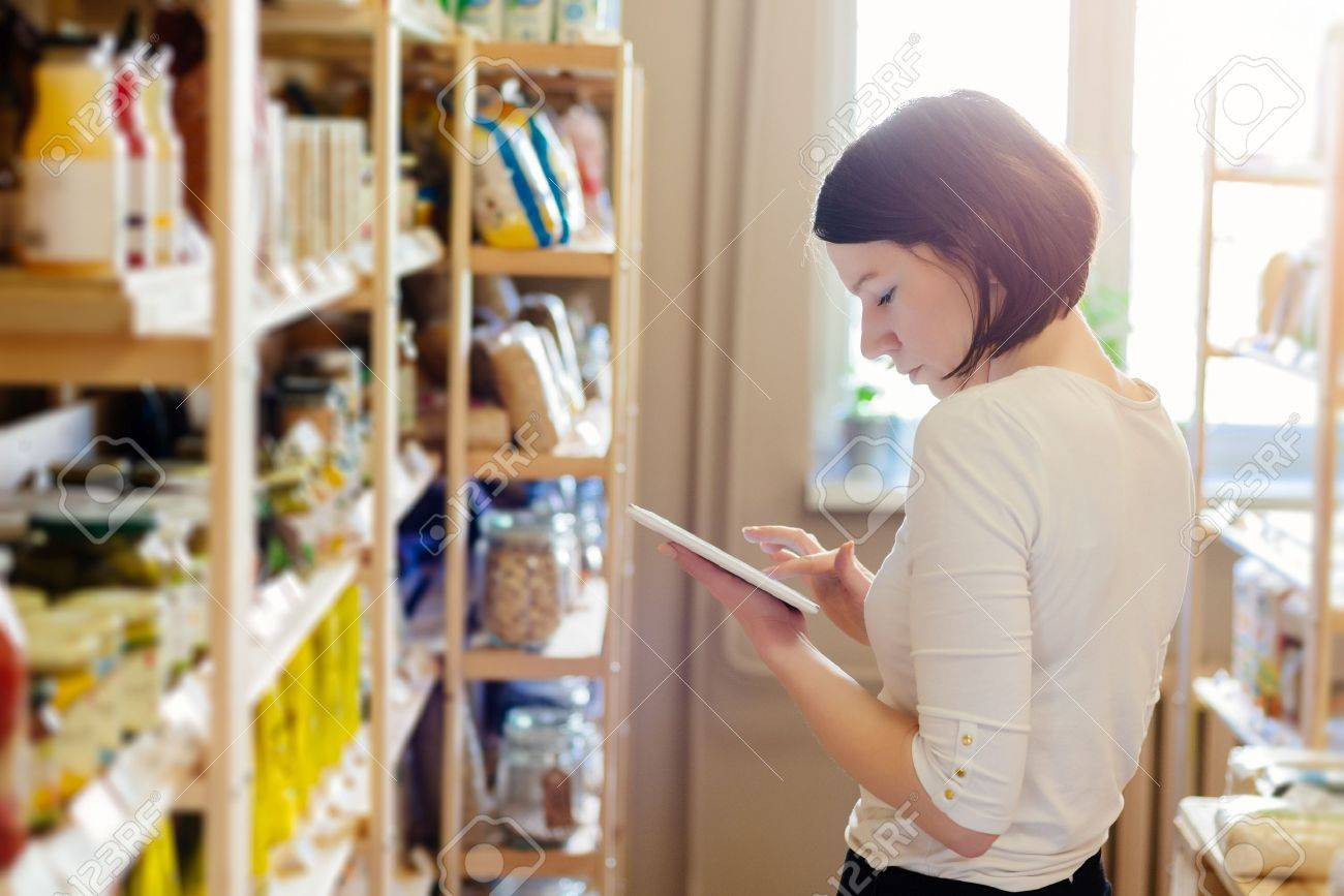 Woman owner of small local grocery store with healthy food ordering products using a tablet. Small Business Concept - 76769139