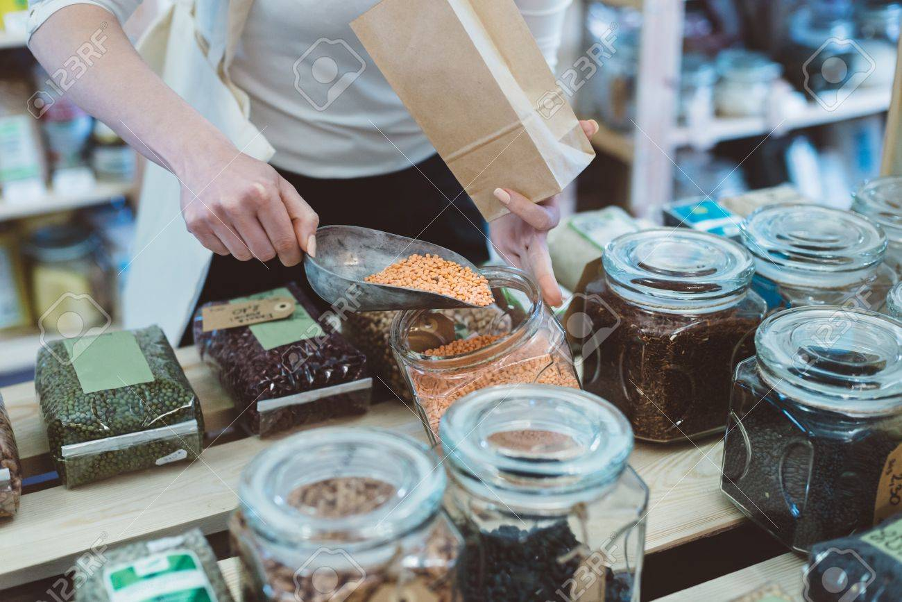 Woman puts lentil seeds into a paper bag in a healthy food store - 80017078