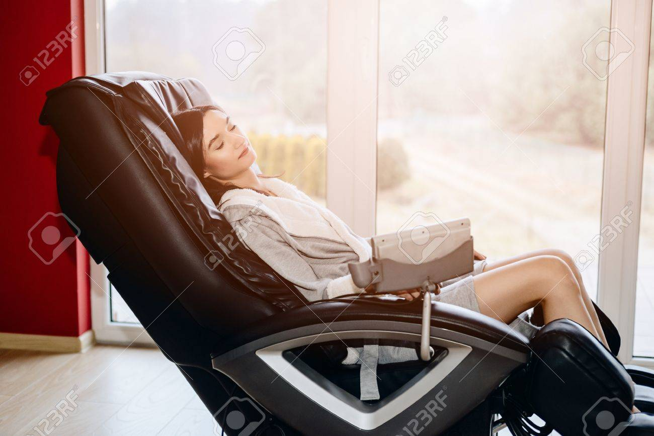Young woman relaxing on the massaging chair at home - 82190477