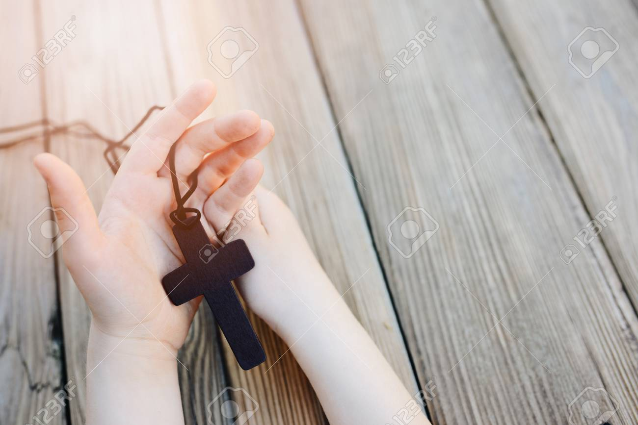 Little childs hands holding wooden rosary. Child praying - 82187103