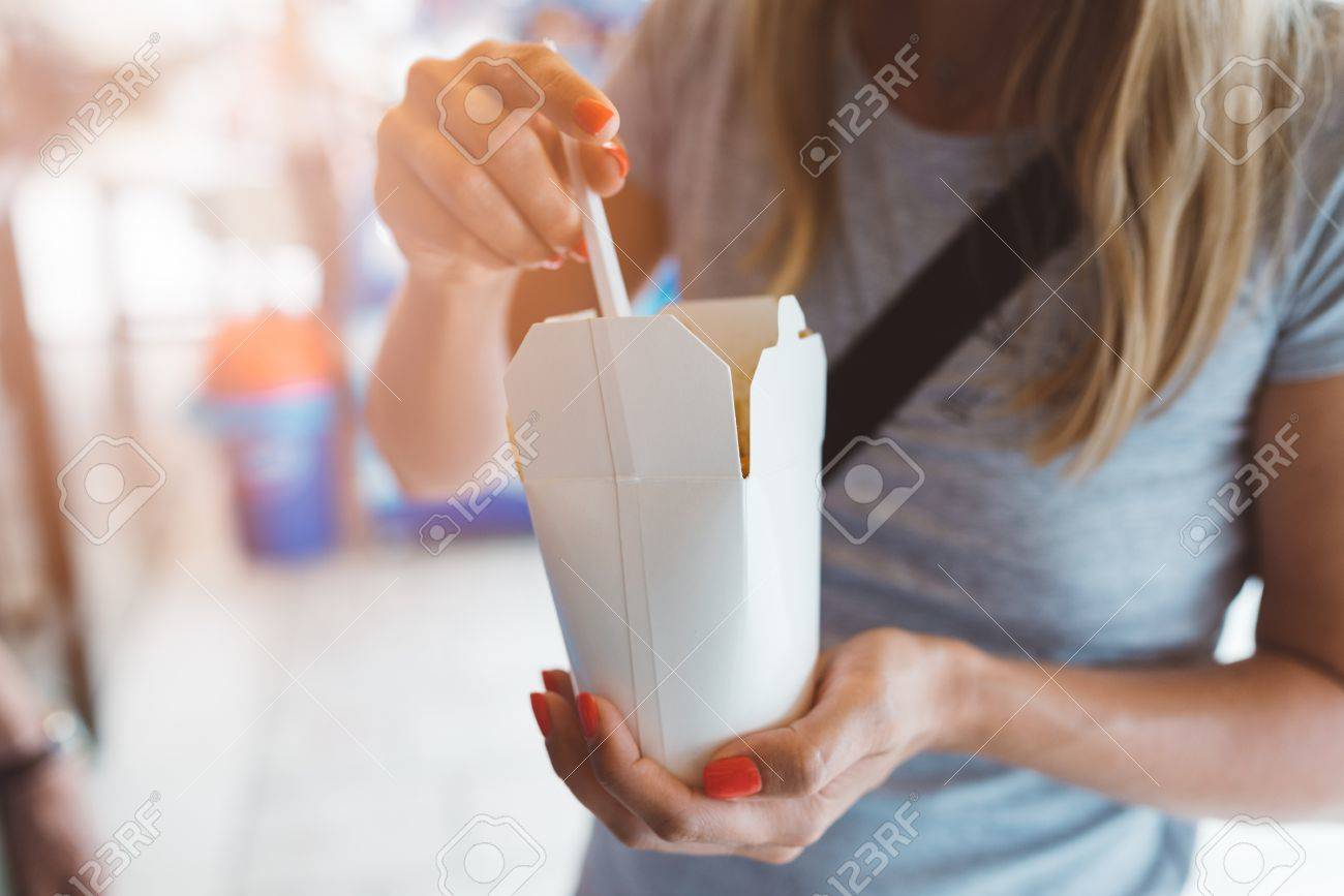 Woman eating fast food noodles from white carton box - 83777965