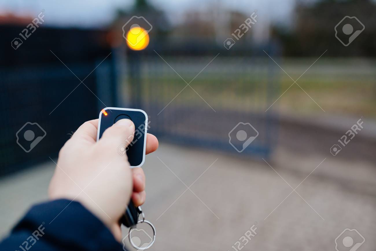 Man opening automatic property gate with remote controller - 91607167