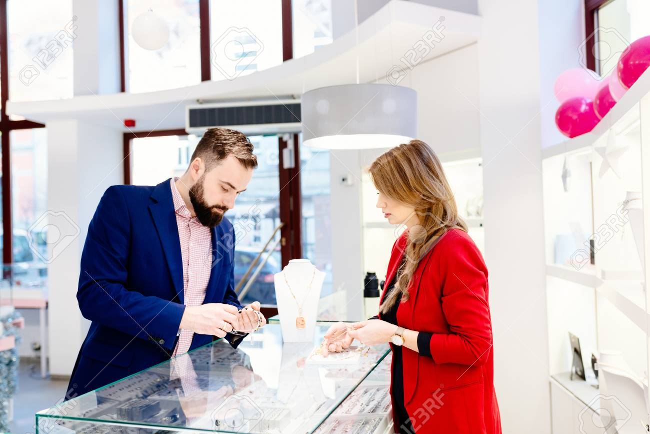 Beauty female seller presents a necklace. Jewelry store. Woman jeweler. Attractive man with a beard choosing a valentine's day gift in jewelry store - 93931120