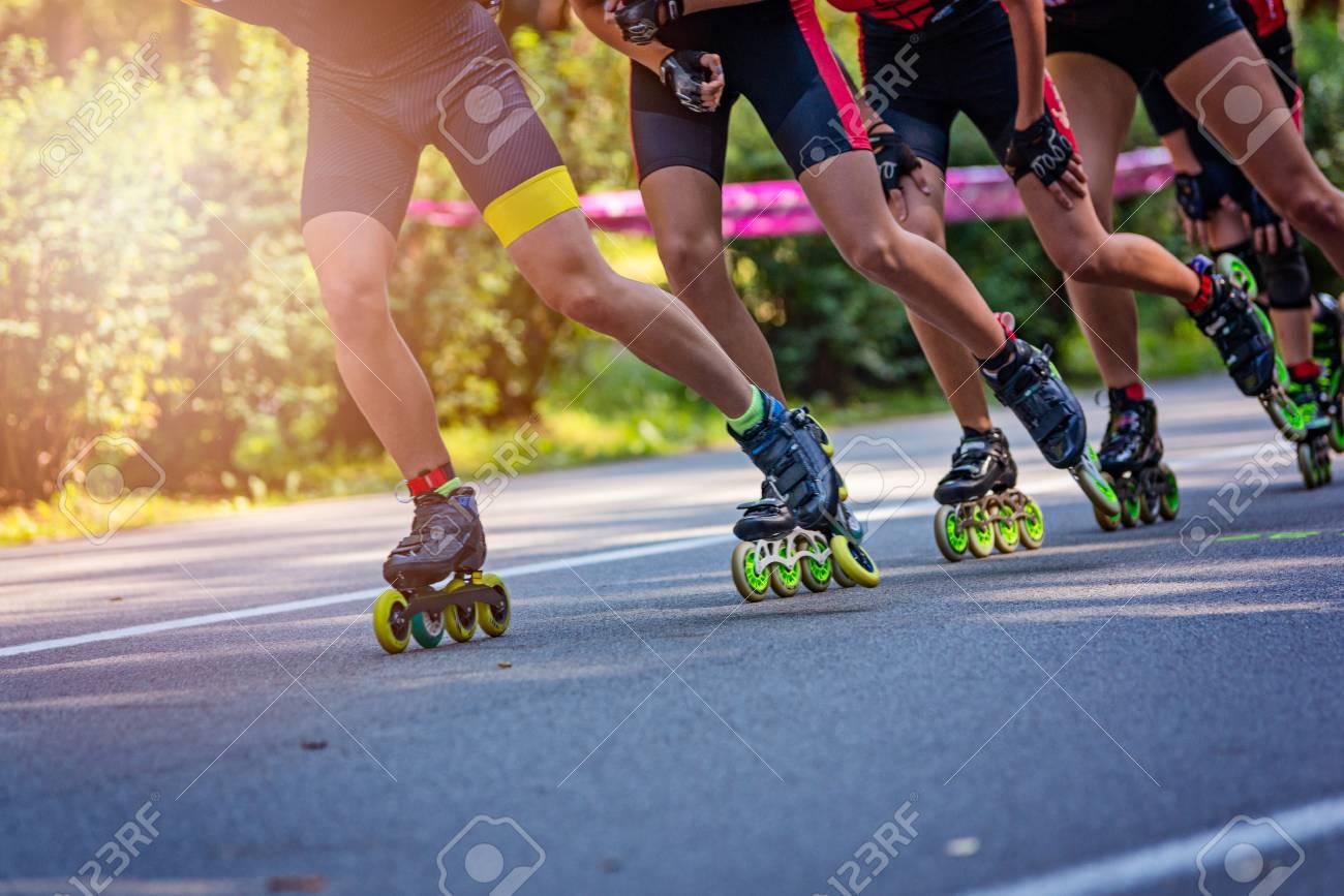 Inline roller skaters racing in the park on asphalt road - 108040301