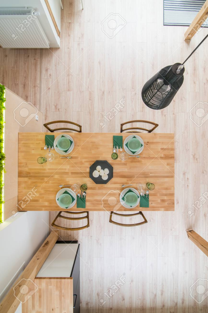 Top view on set wooden dining table. Modern bright flat apartment..