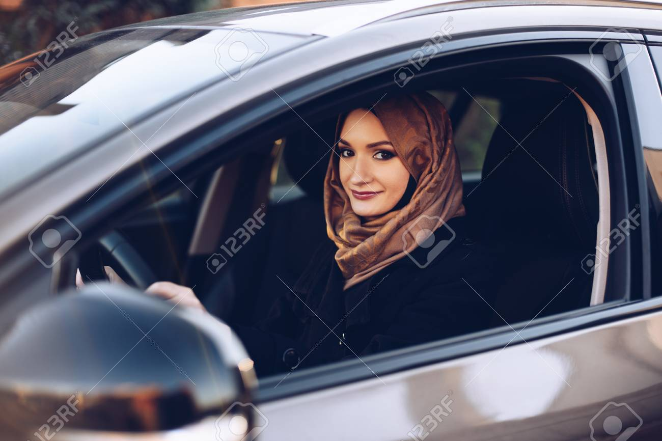 Young arabic woman in hijab driving a car - 114883487
