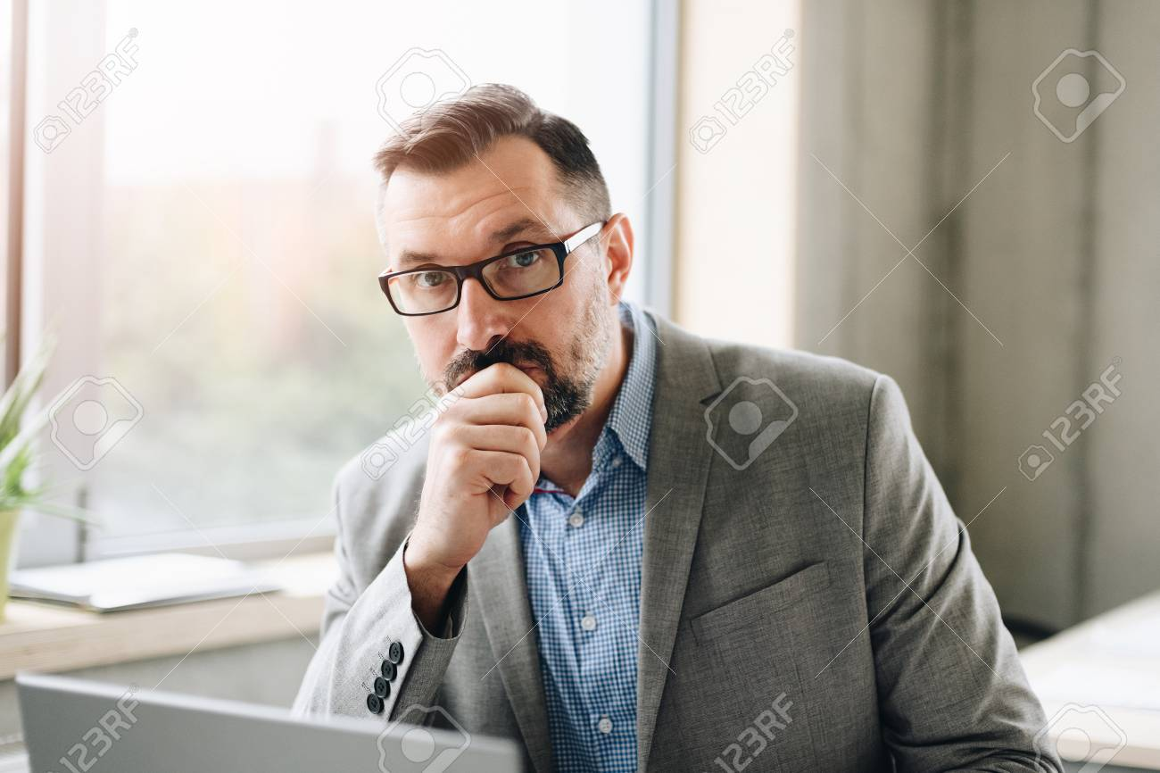 Thoughtful middle aged handsome businessman in shirt working on laptop computer in office. Man working in office - 116596243