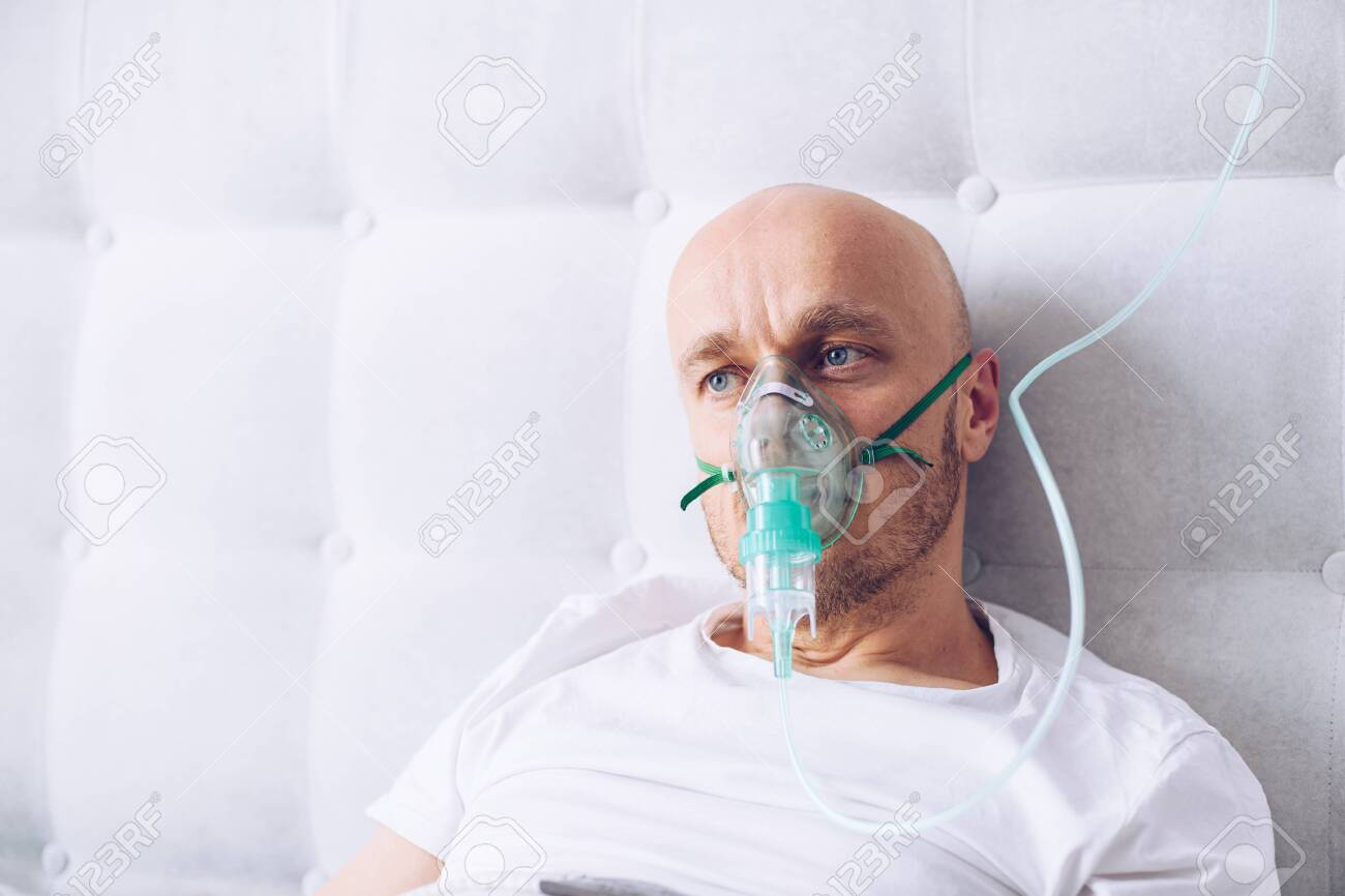 Man breathing through oxygen mask in bed. Covid-19 patient. - 144166174