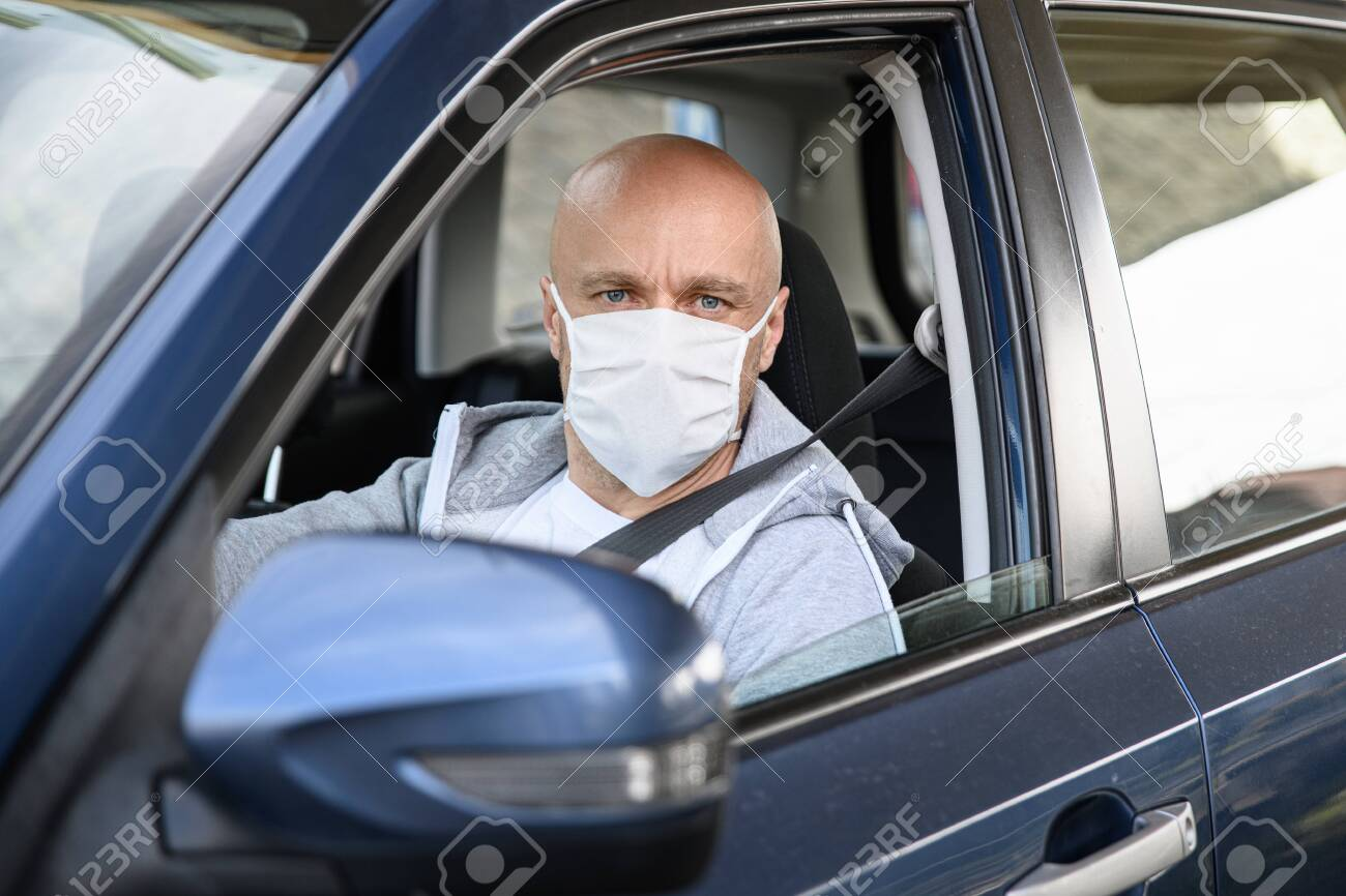 Man driving a car in medical protective mask. - 145297116