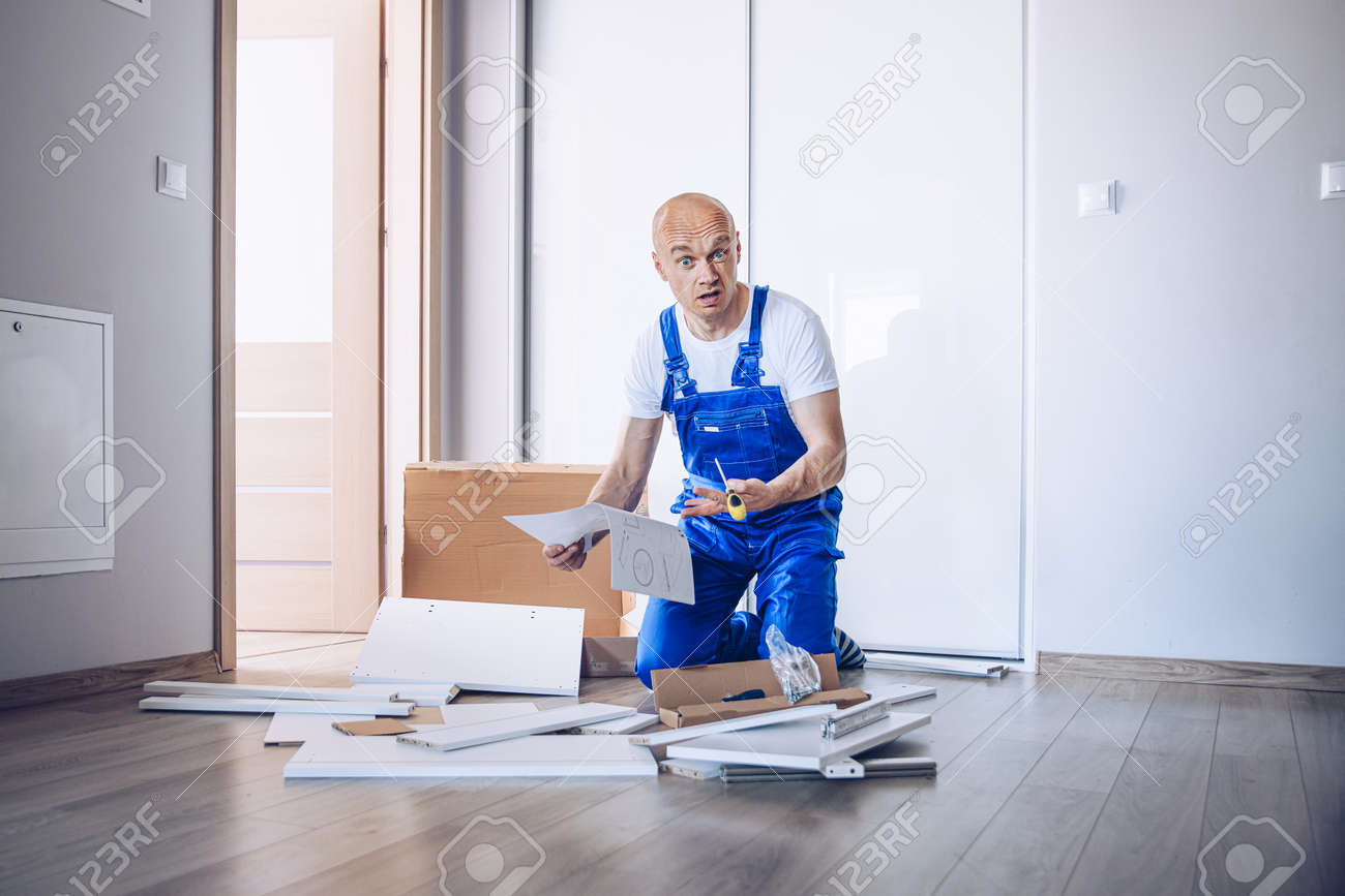 Nervous confused man assembling cabinet at home. - 148154180