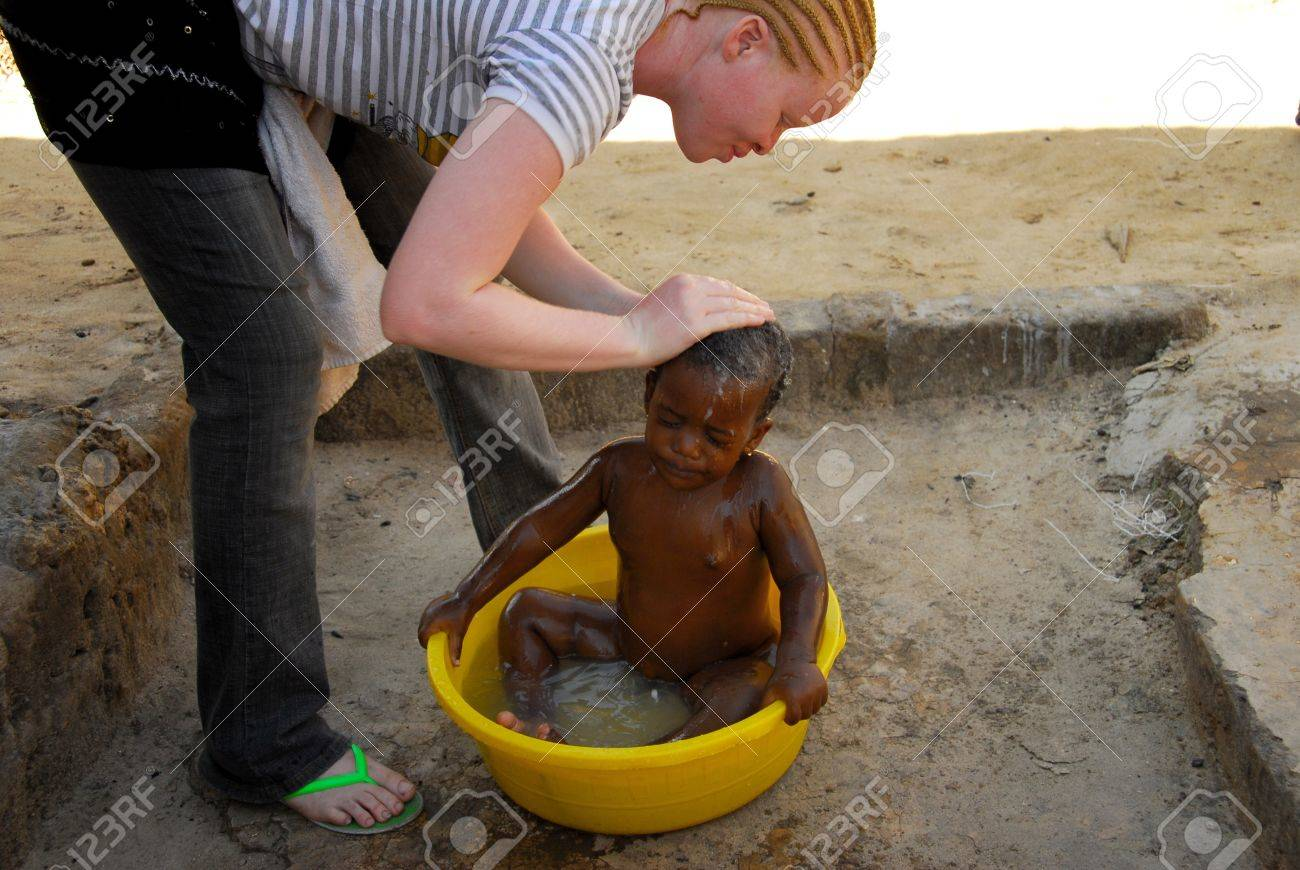 Mwanza,Tanzania, February 8, 2010: Albino girl who washes a baby in the basin.Tanzania is the African region with more albinos. By the year 2006 albino people are killed for witchcraft rituals Stock Photo - 9036381