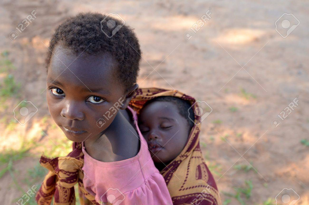 LUSAKA,ZAMBIA � DECEMBER 3,2011: unidentified child with her brother on his shoulders. Many children in Lusaka are out of school to care for siblings when parents work in the fields,  on December 3,2011 in Lusaka,Zambia Stock Photo - 12045800