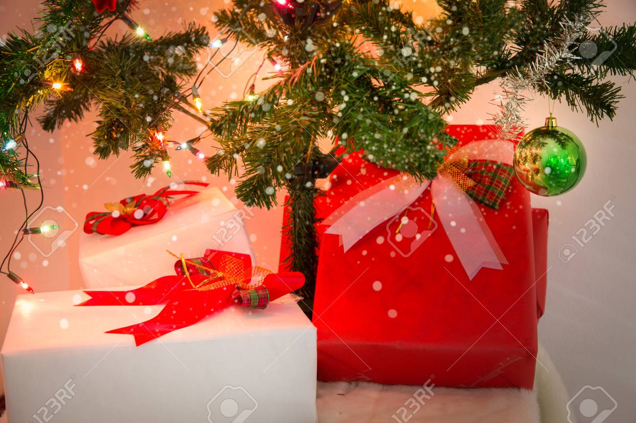 christmas gift box and decorated christmas tree in warm tone photo with snow effect stock photo