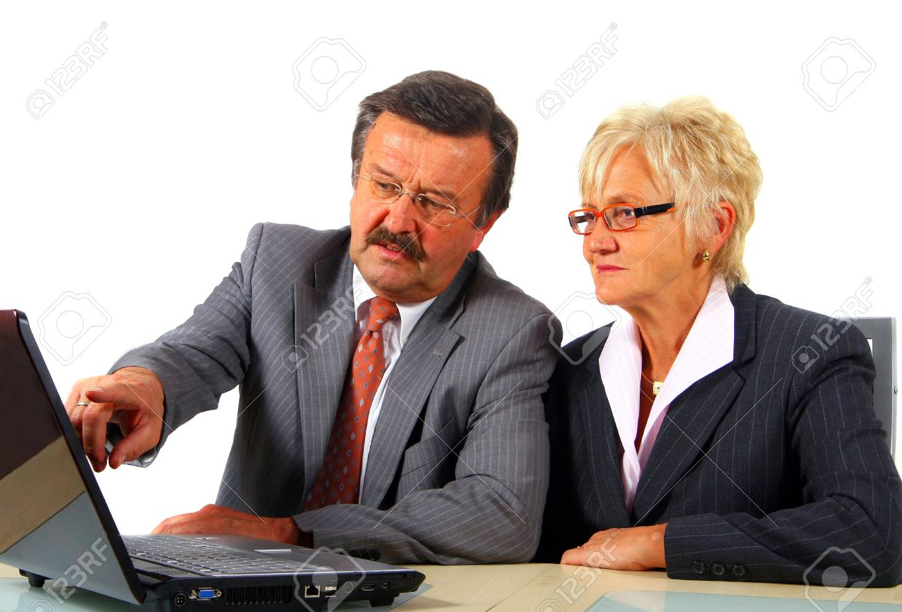 Mature business team - A senior businesswoman in her fitifties is working on a laptopt in an office. Isolated over white. Stock Photo - 3793175