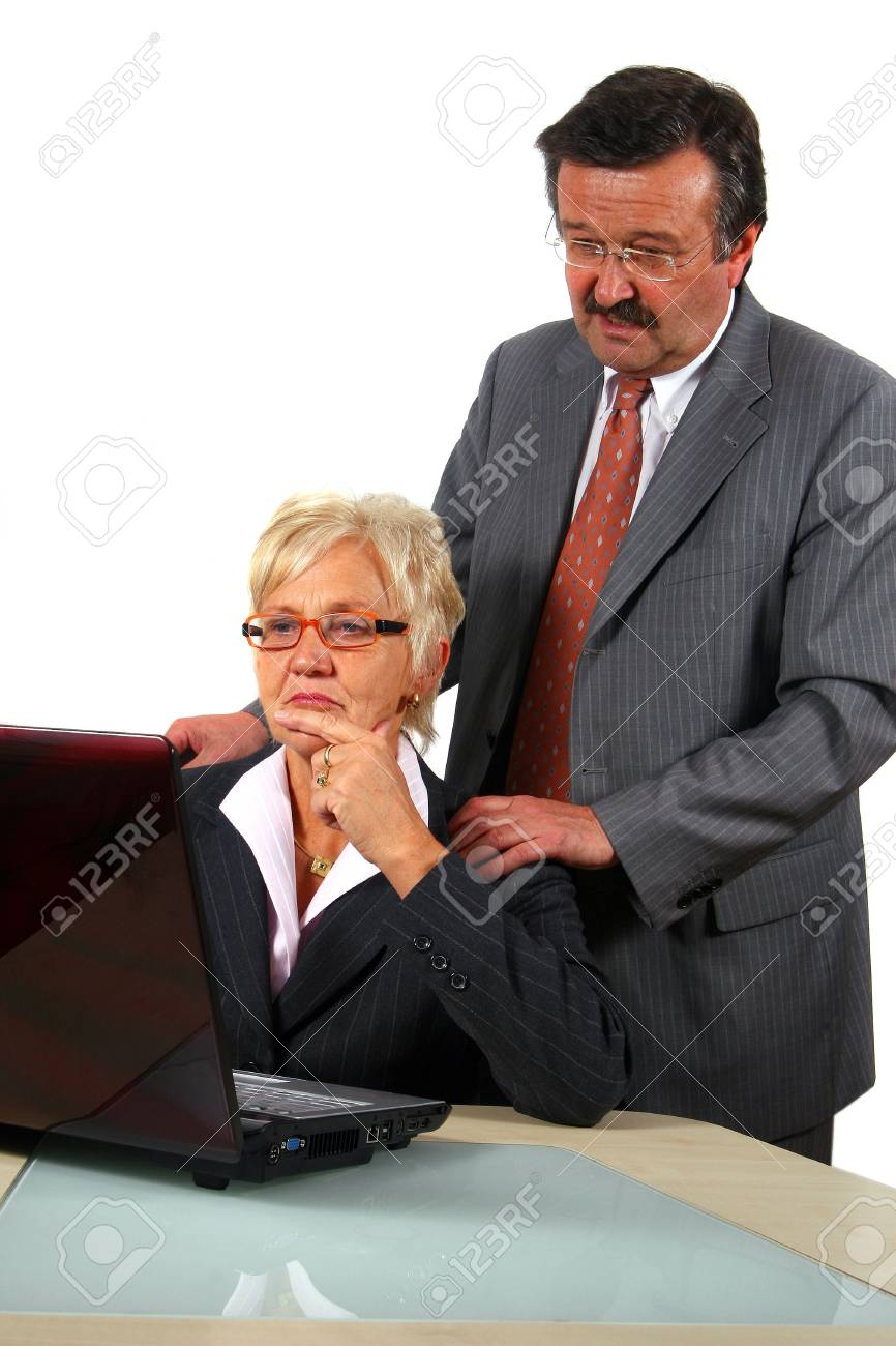 Working Business Team - A business woman and a man in front of a laptop on a desk. The man explains something to the woman. Isolated over white. Stock Photo - 3922651