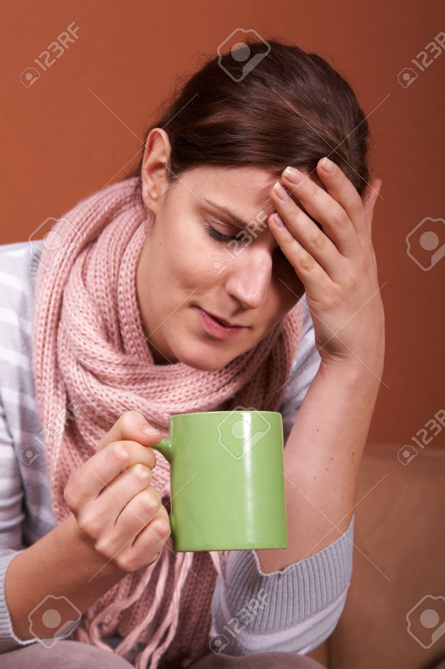 A young sick woman with a cup of tea in her hand. She hold her head in pain. Stock Photo - 4141803