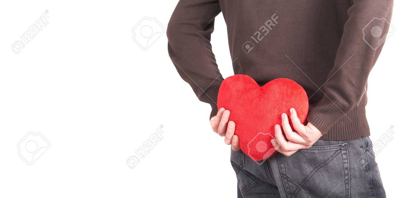 Man Shaped Pillow A Young Man Holds A Heart Shaped Pillow Behind His Back Which