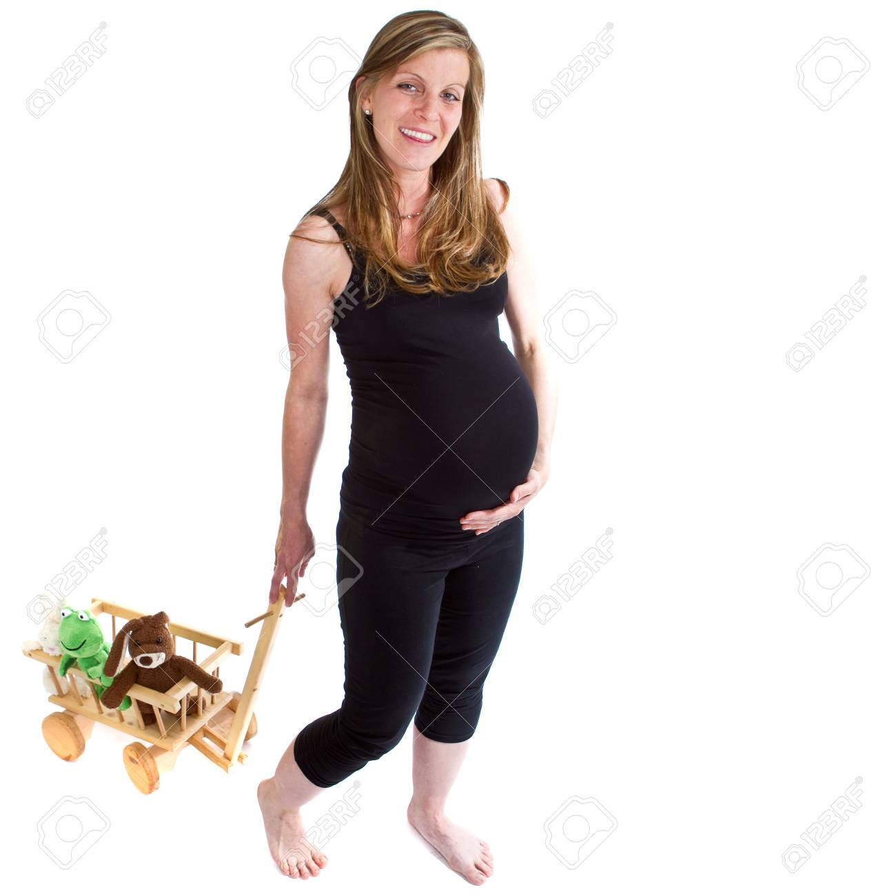 Young fresh pregnant woman is pulling  a trolley filled with toy animals isolated over white background. Stock Photo - 7410088