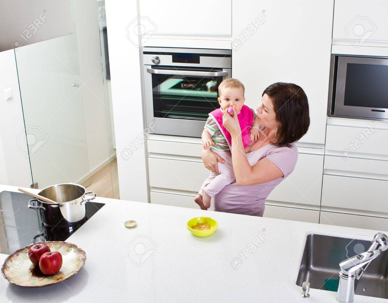 Kitchen Setting Young Mother Is Feeding Her Baby In A Modern Kitchen Setting