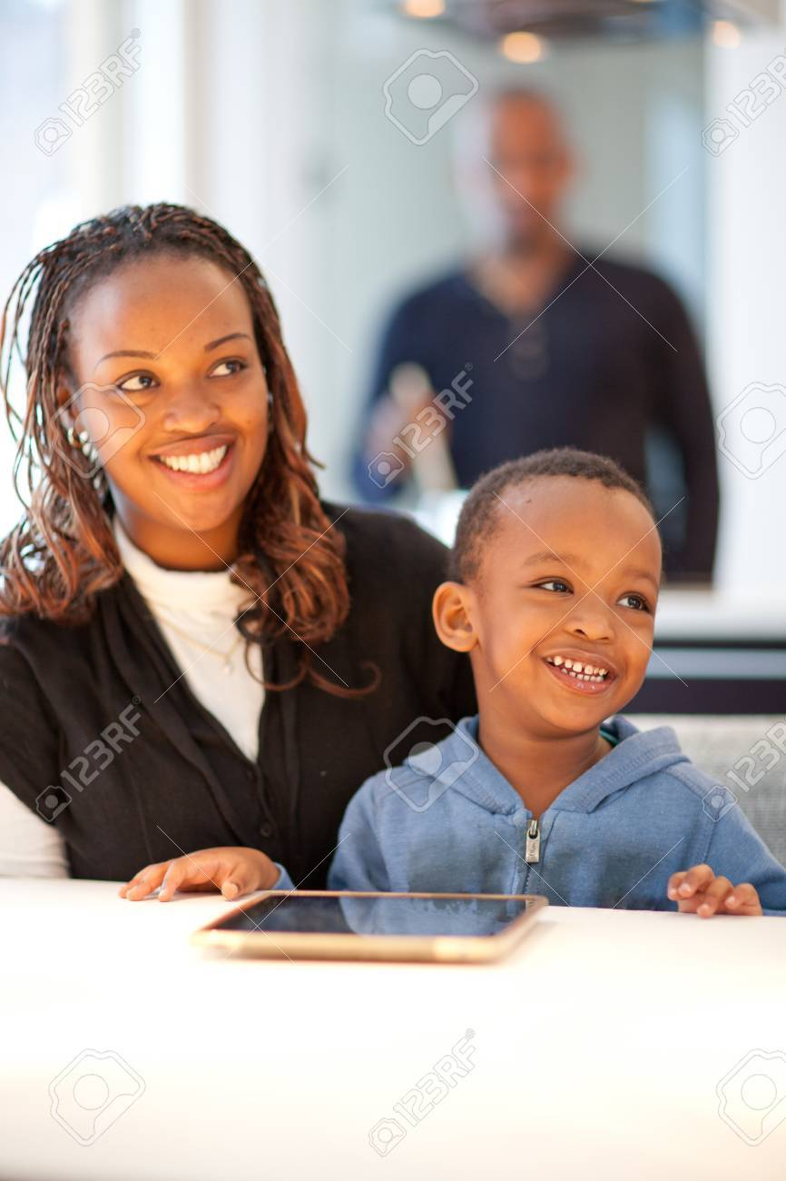 Kitchen setting with young black family playing with a tablet pc. Stock Photo - 12922122