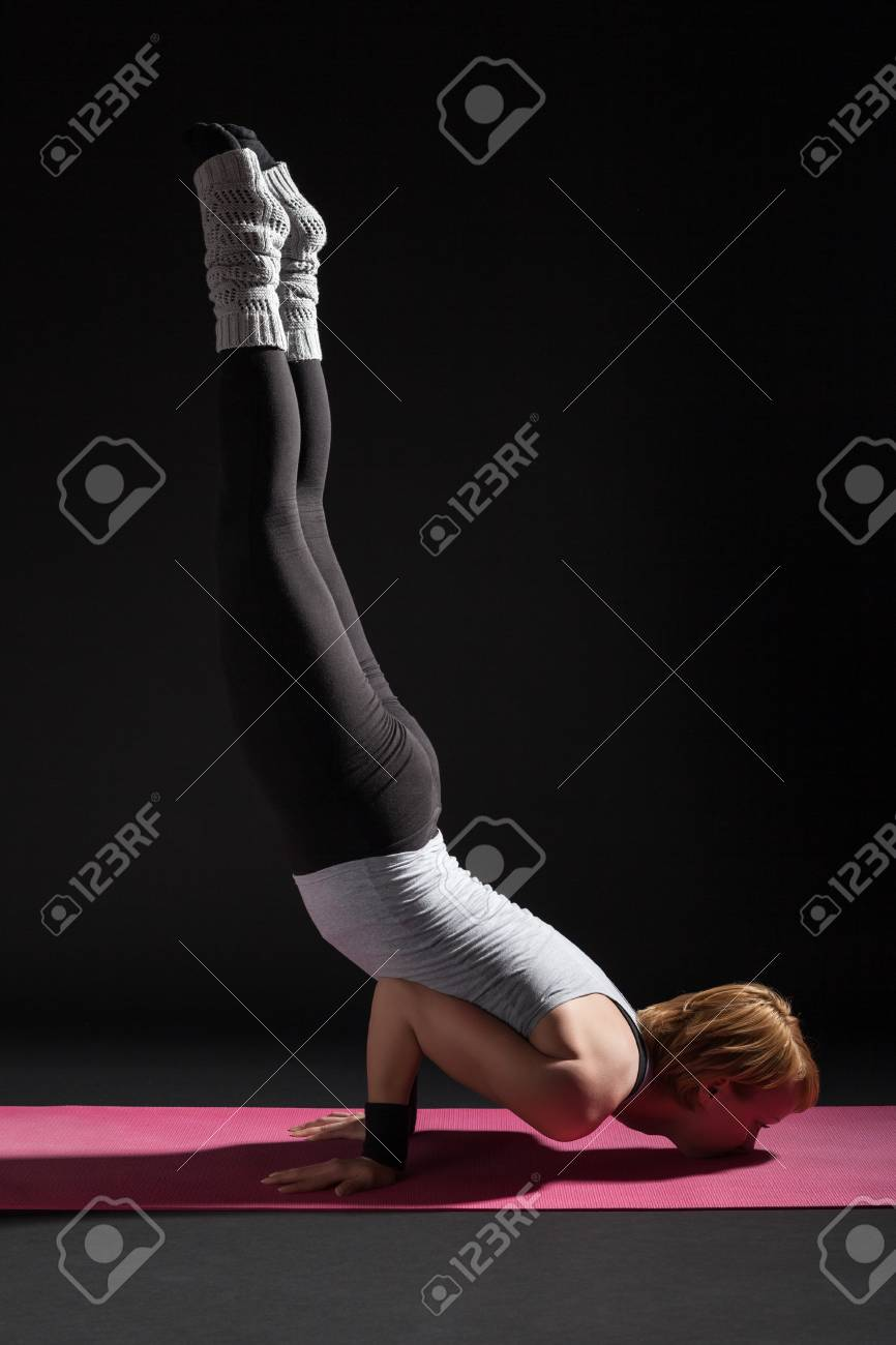 e7f6c67d4219e Stock Photo - Young woman practicing yoga, Vrschikasana / Scorpion pose
