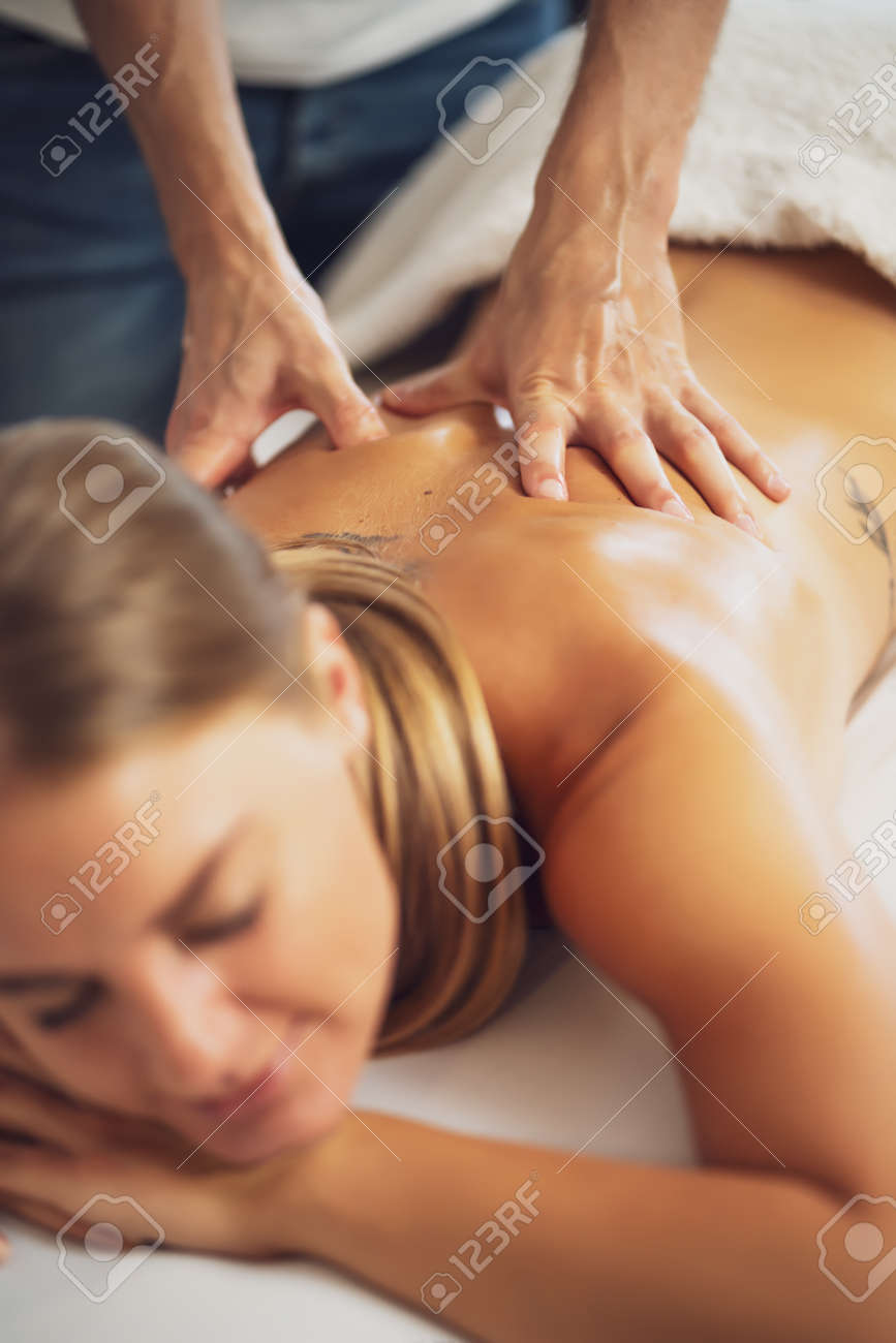 Professional masseur doing therapeutic massage. Woman enjoying massage in her home. Young woman getting relaxing body massage. - 165810195