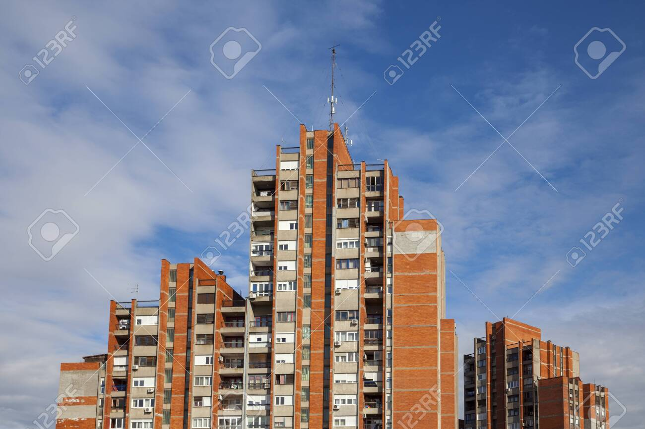 a group of buildings with a red facade brick against a blue sky - 143822405