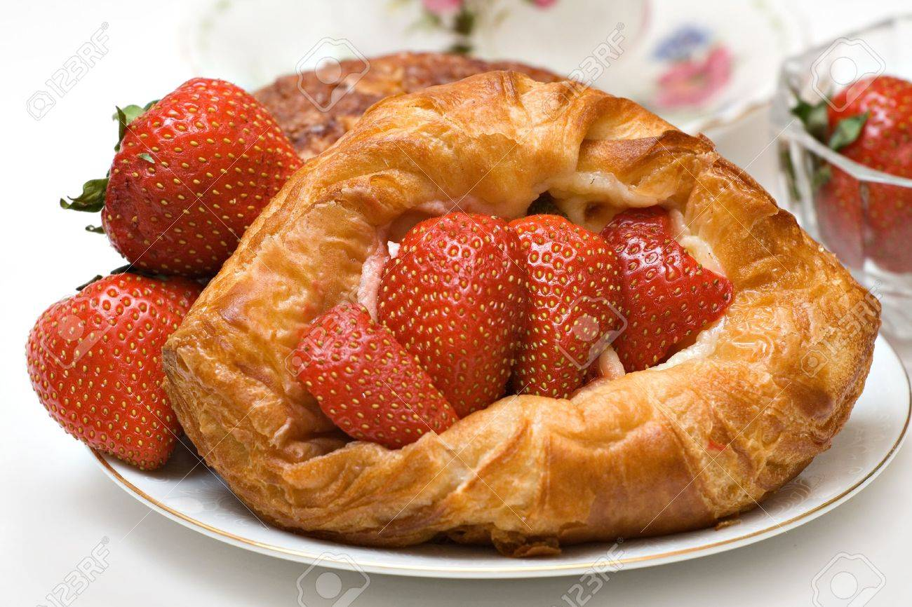 Variety of pastries featuring a strawberry danish - fresh strawberries cup saucer visible. Stock Photo - 1011002