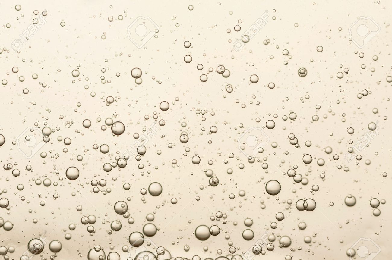 Many small champagne bubbles in a glass of champagne - 50022936