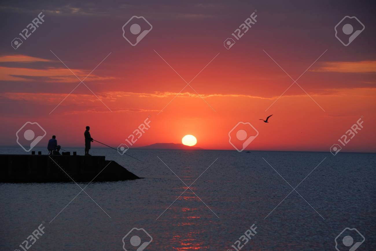 Sea sunrise and two men fishing Stock Photo - 2102667