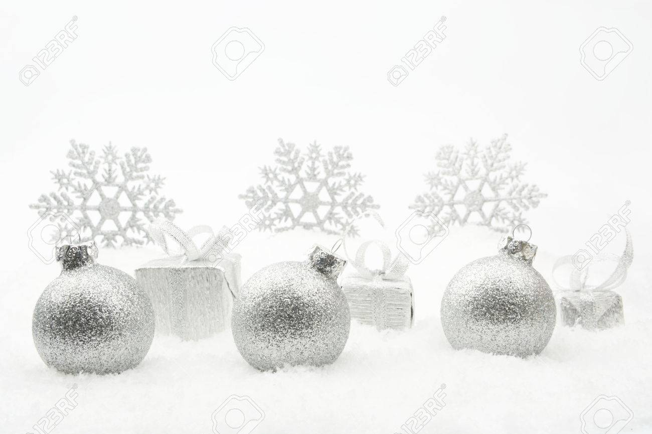 088559d7cb447 Decoration of silver christmas gifts and baubles and snowflakes on snow on white  background Stock Photo