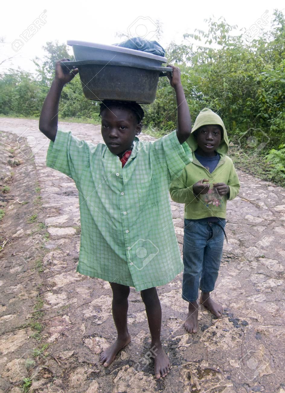 MILOT, HAITI - NOV 17, Unidentified Haitian kids carrying their goods on a steep mountain road on November 17, 2013 in Milot, Haiti Stock Photo - 24270312