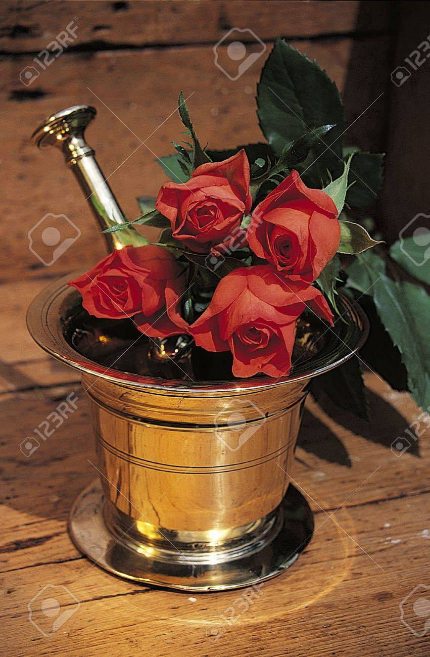A rustic brass pestle and mortar with red roses, shot on a background of antique wood furniture Stock Photo - 276039