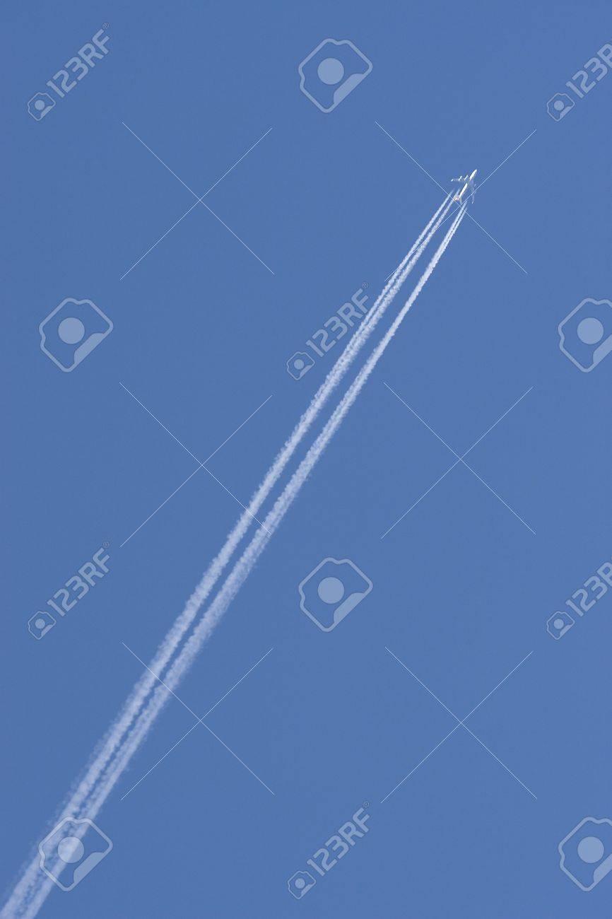 A Jumbo Jet leaving a vapour trail across a deep blue sky Stock Photo - 300429