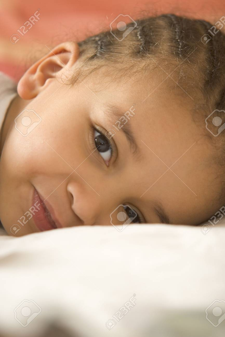 A beautiful young mixed race girl lying on her pillow having just woken up Stock Photo - 318352